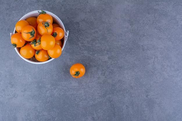 Желтые помидоры черри, изолированные на синей поверхности