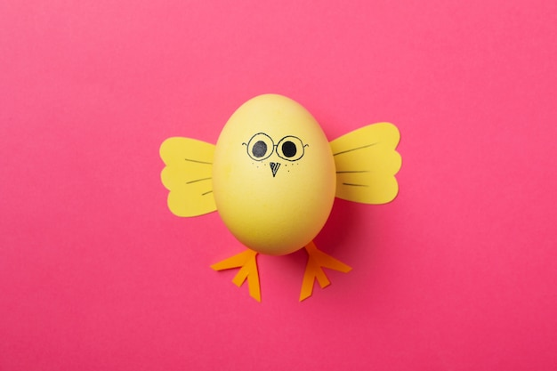 Yellow chick made of egg on pink surface