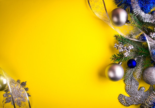 Yellow christmas background decorated with fir tree and toys