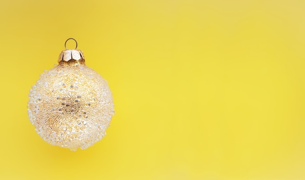 Желтый рождественский шар с некоторыми шишками на зеленом фоне минимальный рождественский дизайн место для текста