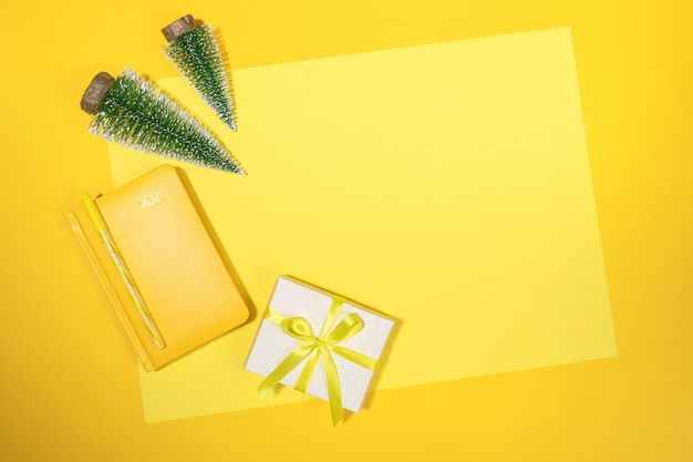 Yellow christmas workspace backdrop. frame of yellow notepad - organizer on 2021, small xmas trees and diy gift box on yellow sheet with copy space. summing up, planning. top view, flat lay.