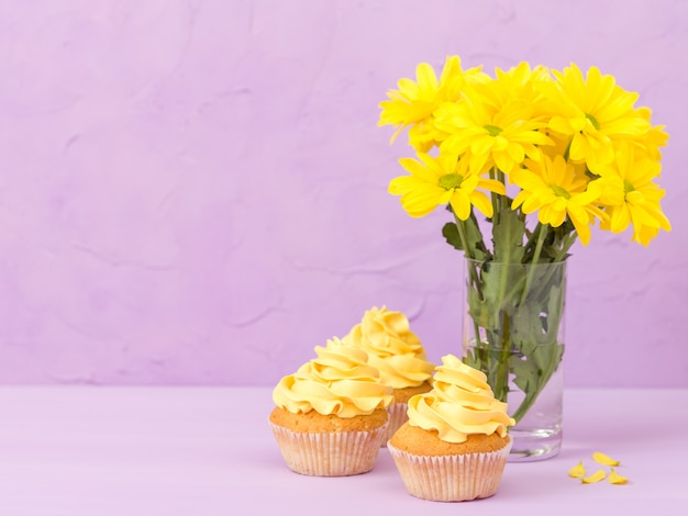Yellow chrysanthemum in glass and sweet cupcake with yellow cream on violet pastel background