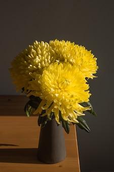 테이블 근접 촬영에 노란 국화 아름다운 밝은 국화 꽃 그림자 국화 벽 수직