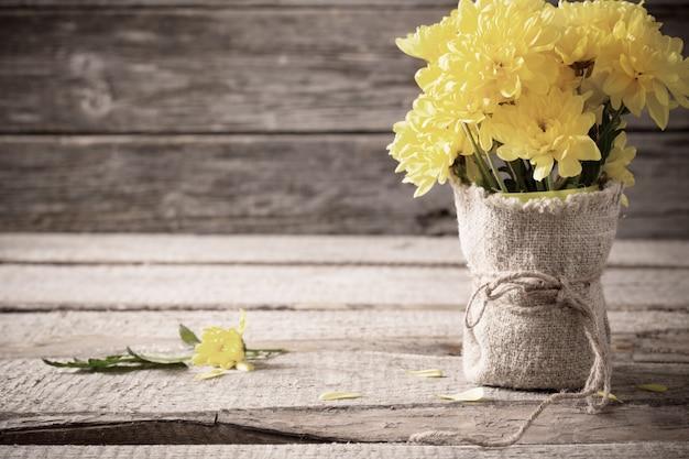 Желтая хризантема на деревянном фоне