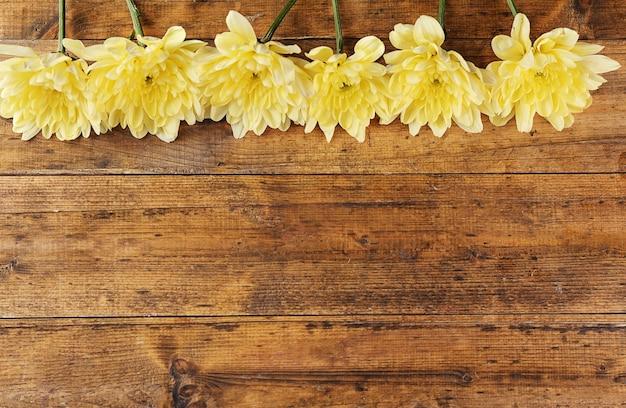 나무 테이블에 노란 국화