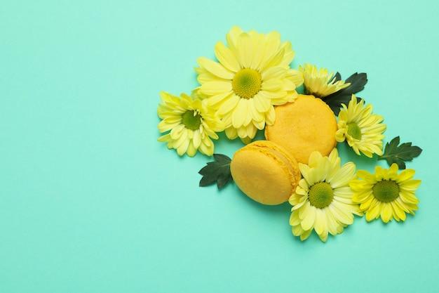 ミントの背景に黄色の菊とマカロン。