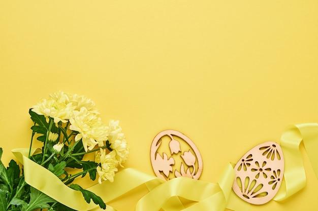 黄色の背景に美しい幅の広いリボンと装飾的なイースターエッグと黄色の菊の花の花束。コピースペース付きグリーティングカードテンプレート