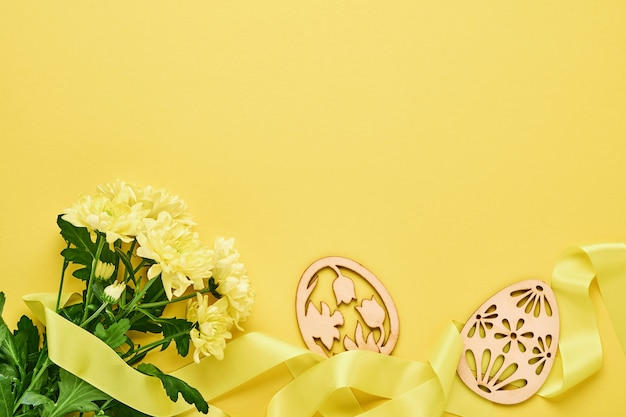Yellow chrysanthemums flowers bouquet with beautiful wide ribbon and decorative easter eggs on yellow background. greeting card template with copy space