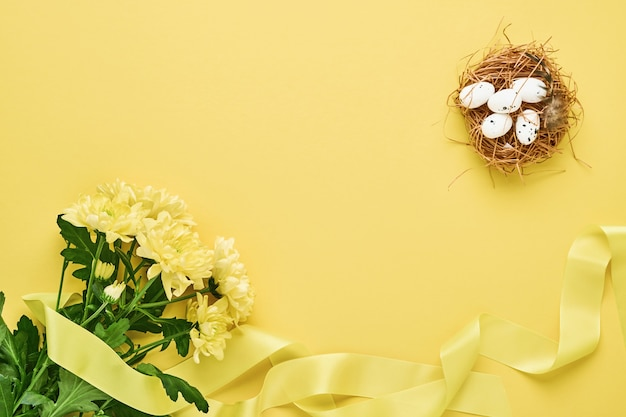 Yellow chrysanthemums flowers bouquet with beautiful wide ribbon and nest with easter eggs on yellow background. greeting card template with copy space