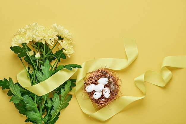 Yellow chrysanthemums flowers bouquet with beautiful wide ribbon and nest with easter eggs on yellow table. .