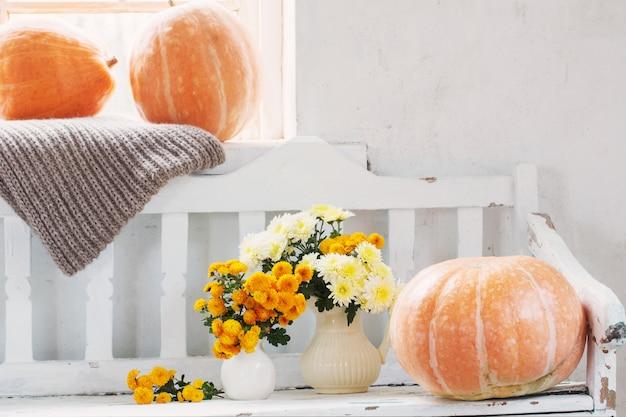 水差しと古い白い木製のベンチにオレンジ色のカボチャの黄色の菊