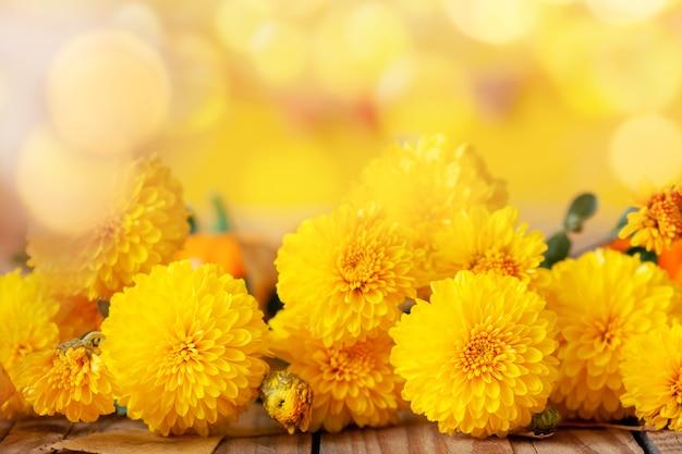 나무 테이블에 노란 국화입니다.