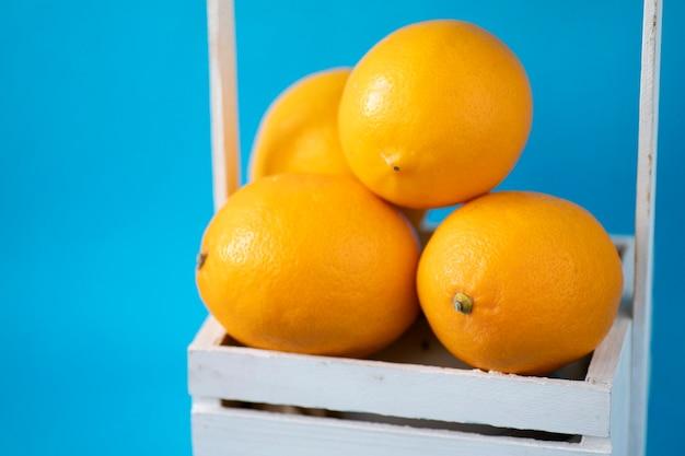 노란색 감귤류. 흰색 바구니에 익은 고 달콤한 오렌지 클로즈업.