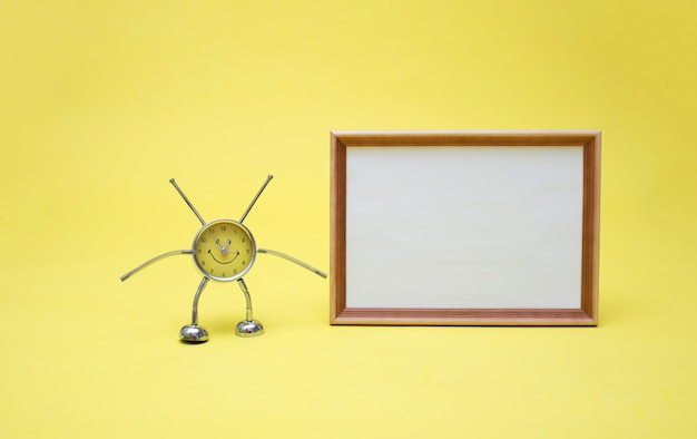 A yellow clock and a frame with an empty white sheet. clock and frame on a yellow space. yellow clock in the shape of a man.