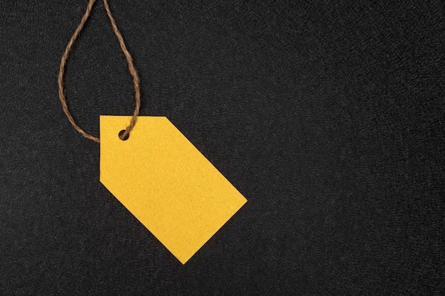 Yellow clothing tag on black background. label blank mockup template.