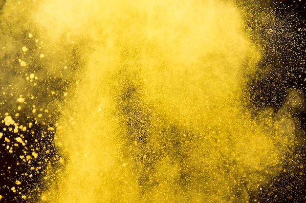 Yellow cloud of cosmetic powder on black background