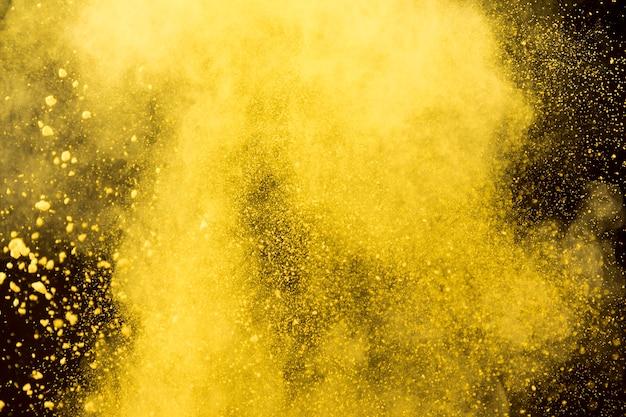 Желтое облако косметической пудры на черном фоне