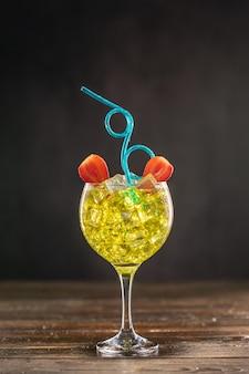 파란색 곱슬 파티 유연한 플라스틱 빨대와 딸기로 장식 된 얼음으로 채워진 유리에 노란색 칵테일