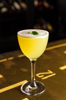 A yellow cocktail in a nick and nora glass garnished with cilantro at the bar