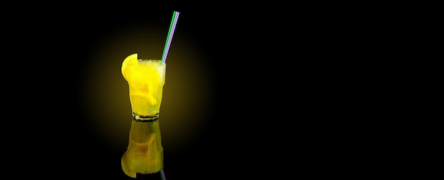 Yellow cocktail with lemon slice, summer refreshing lemonade with straw, over black background