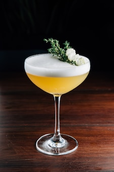Yellow cocktail with white foam decorated with white flower and green branch. studio shot.