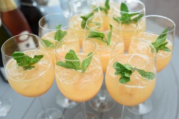 Желтые коктейли с листьями мяты в очках на столе в помещении