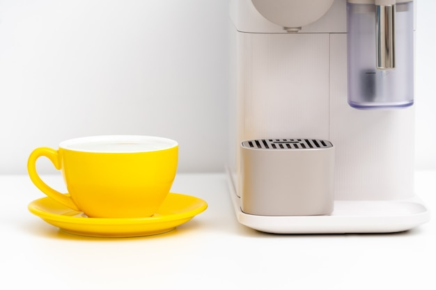 Yellow coffee cup and coffee capsule machine