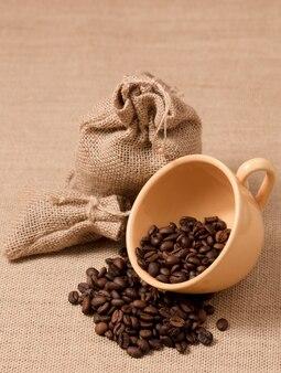 Желтая кофейная чашка с зернами и тканевые мешки из рафии