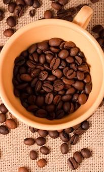Желтая кофейная чашка с зернами и фоном ткани из рафии