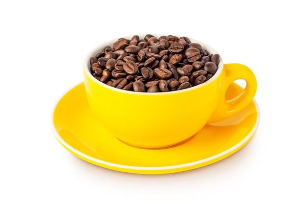 Желтая кофейная чашка с цельными кофейными зернами, изолированными на белом