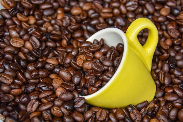 Желтые кофейные чашки и кофейные зерна арабики, прошедшие термообработку до измельчения.