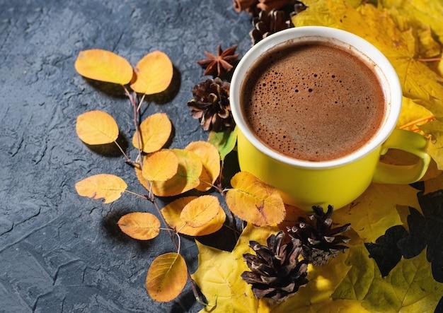 Желтая кофейная кружка на темном каменном столе с осенними листьями, корицей и copyspace