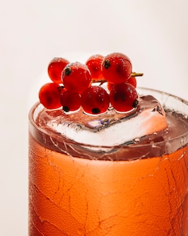 Yellow cold refreshment drink with berries and ice cubes.