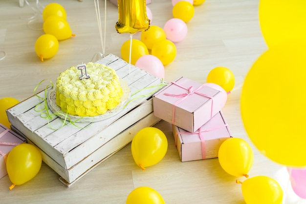 Yellow color concept of festive decorations with cake and candles 1 year