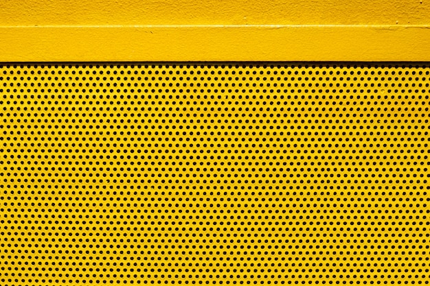 Yellow color metal plate with many small circular holes dots texture for background