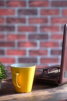 Yellow color mug mockup with with laptop and notepad on table