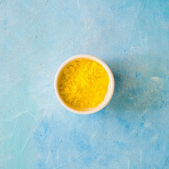 Yellow color powder in white bowl on blue concrete backdrop