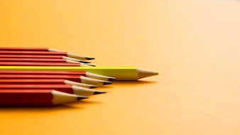 Yellow colored pencil lying between red pencil against yellow background