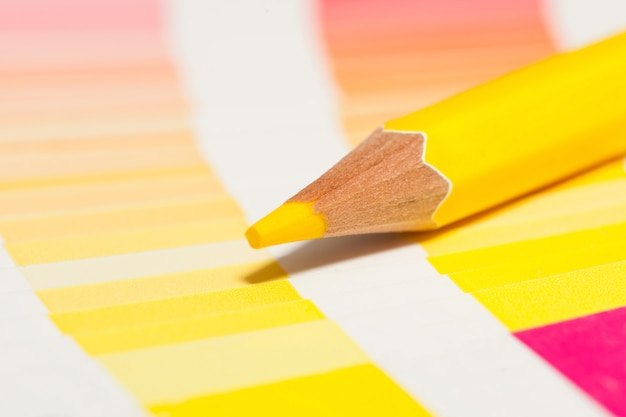 Yellow colored pencils and color chart of all colors