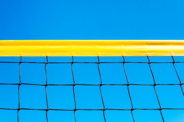 Yellow colored summer games ball background - beach volleyball or tennis net against blue sky for sport events. copyspace. copy space