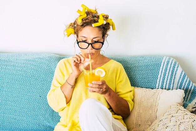 컬러와 블루 소파와 함께 집에서 건강한 오렌지 주스를 마시는 아름다운 백인 젊은 성인 여자의 노란색 색상 초상화