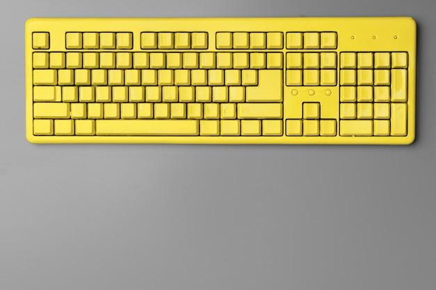 灰色の背景に黄色のコンピューターのキーボード