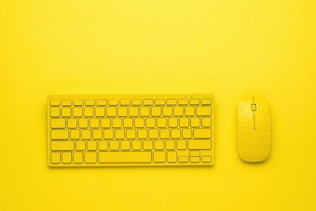 Желтая компьютерная мышь и клавиатура на желтом фоне.