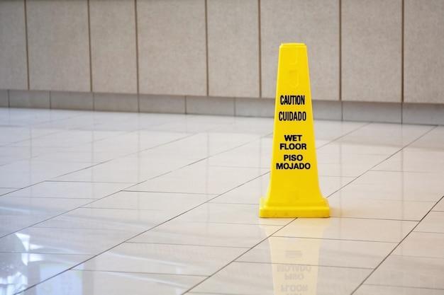 Желтый конус, предупреждающий о мокром полу на английском и испанском языках в отеле.