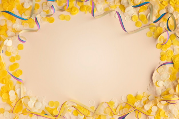 Yellow confetti and ribbons copy space top view