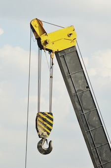 A yellow construction crane with hook against the sky