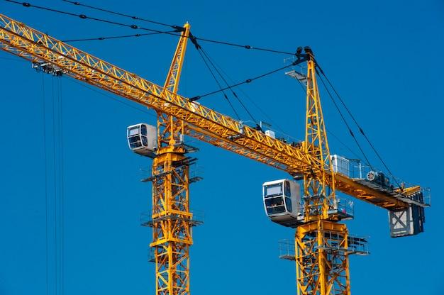 Yellow construction cranes against a blue sky