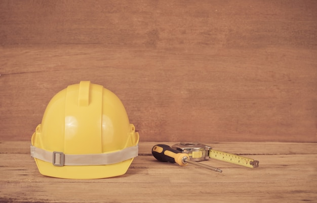 Yellow construction safety helmet on wood