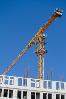 Желтый строительный башенный кран возле нового здания над голубым небом, выборочный фокус