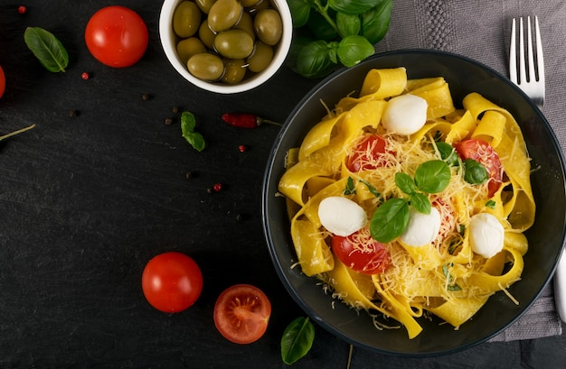 黒のボウルの上面図にある黄色の調理済みパスタパッパルデッレ、フェットチーネ、またはタリアテッレ。